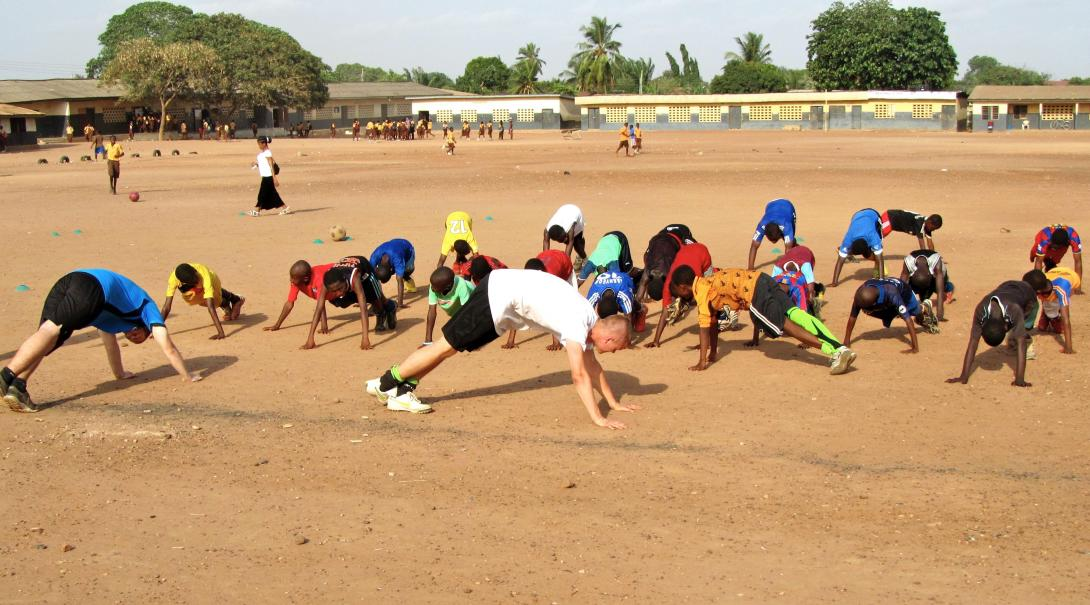 A Projects Abroad teaching volunteer gets involved in a sports lesson in Ghana.